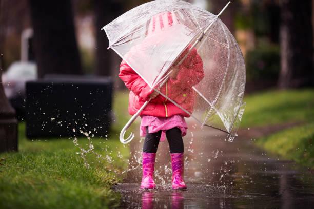 junges mädchen spielt in der viel california regen benötigt. - kinder winterstiefel stock-fotos und bilder