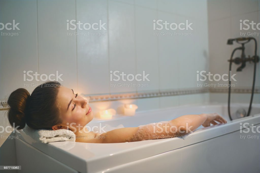 Young girl is resting in a bathtub with foam  with candle stock photo