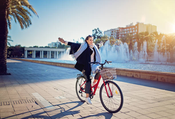Young girl is riding a bicycle without hands in the park stock photo