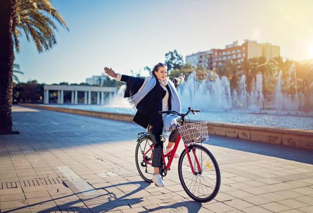 Jovem é andar de bicicleta sem as mãos no parque - foto de acervo