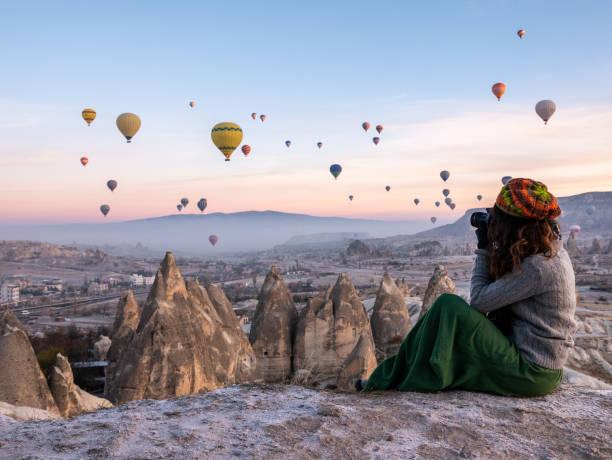 jong meisje is het schieten van foto's van hete lucht ballonnen vliegen in rode en rose valley in goreme in cappadocië in turkije - aardpiramide stockfoto's en -beelden