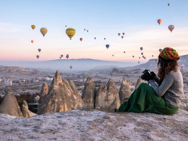 young girl is shooting photos of hot air balloons flying in red and rose valley in goreme in cappadocia in turkey - турция стоковые фото и изображения