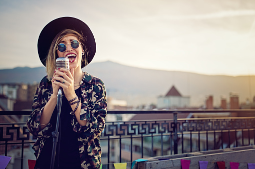 Young girl is singing on the roof terrace party