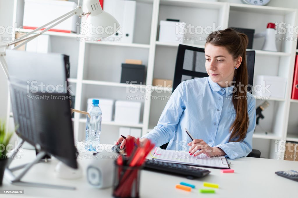 A young girl is sitting at a table in the office, holding a pen in her hand and working at the computer. - Royalty-free Advice Stock Photo