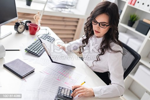 istock A young girl is sitting at the office desk and is blessing on the calculator. 1001814086