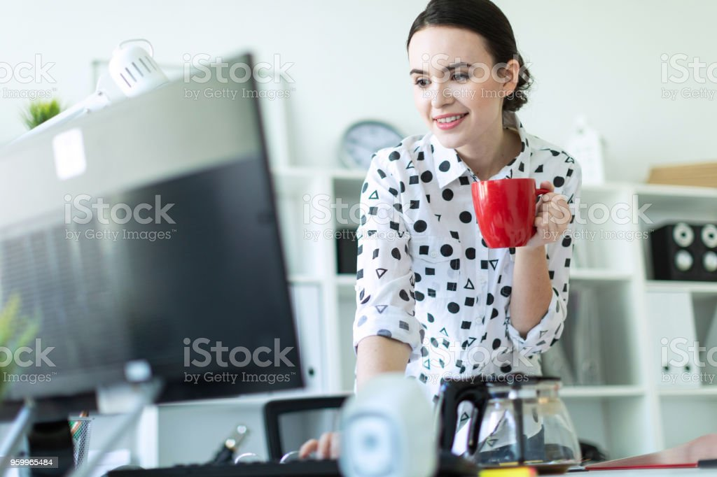 A young girl is standing in the office near the table, holding a red mug in her hand and typing on the keyboard. stock photo