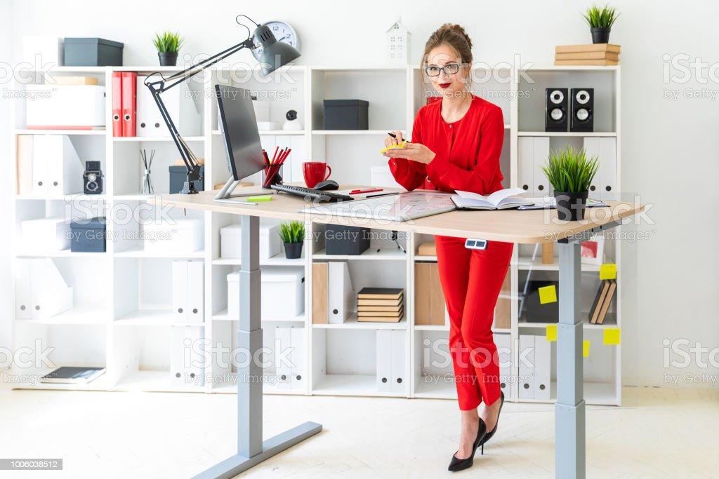 Une jeune fille est debout près d'une table dans le bureau, tenant des autocollants et un marqueur noir. La jeune fille travaille avec un ordinateur, le bloc-notes et un tableau magnétique. photo libre de droits