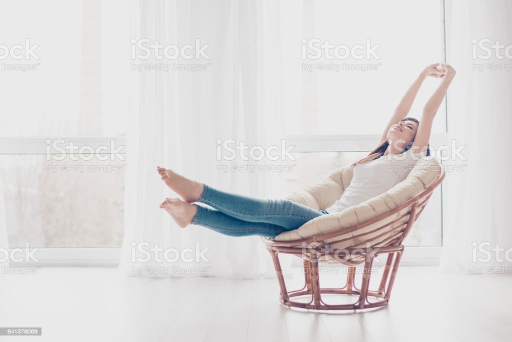 Young girl is stretching in modern armchair in light livingroom. She is sleepy and dreamy, wearing casual clothes stock photo