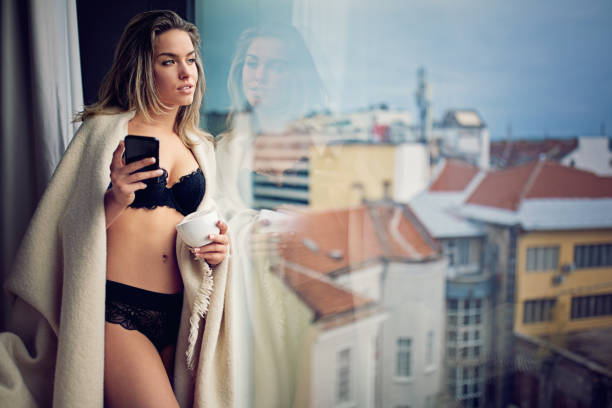 Young girl is texting and drinking coffee at the window in the morning Young girl is texting and drinking coffee at the window in the morning lingerie stock pictures, royalty-free photos & images