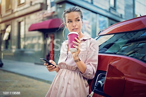 Young girl is texting until waiting her electric car to charge