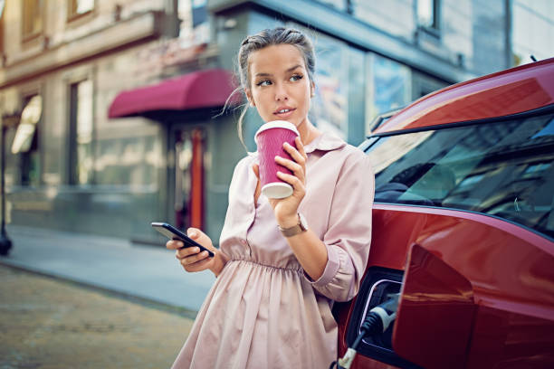 Young girl is texting until waiting her electric car to charge Young girl is texting until waiting her electric car to charge hybrid car stock pictures, royalty-free photos & images