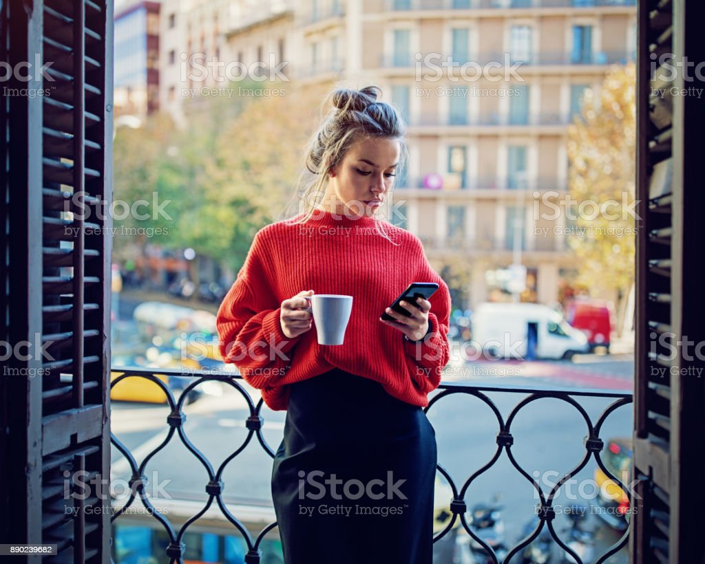 Young girl is texting using her mobile phone at the balcony - Foto stock royalty-free di Adulto