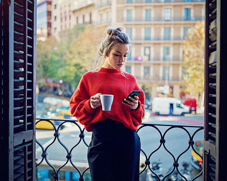 Young Girl Is Texting Using Her Mobile Phone At The Balcony - Fotografie stock e altre immagini di Adulto