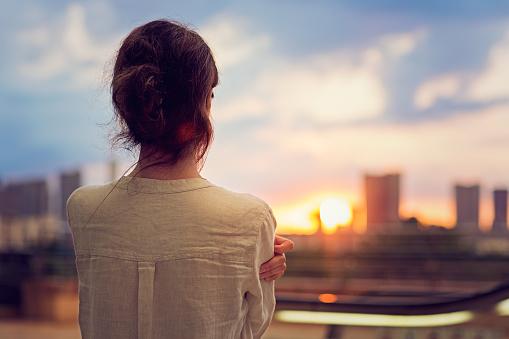 若い女の子に沈む夕日をご覧になるのは東京 - 1人のストックフォトや画像を多数ご用意