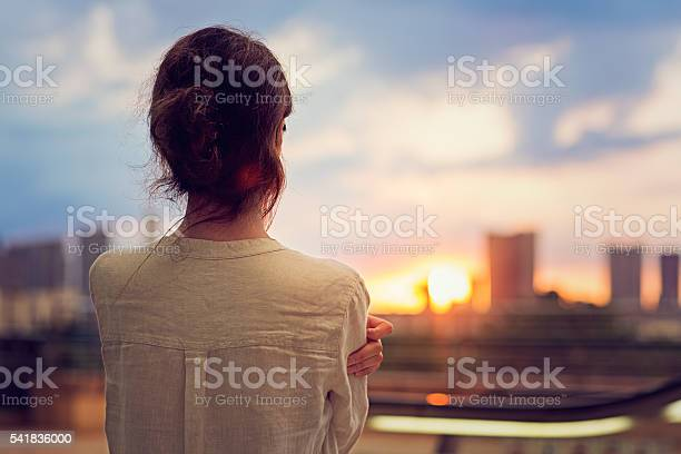 Photo of Young girl is watching sunset over Tokyo