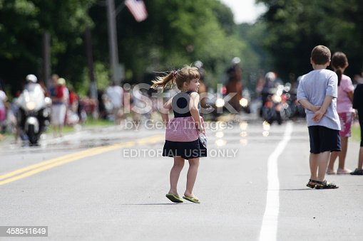 istock Young Girl Jumping for Joy at the July 4th Parade 458541649