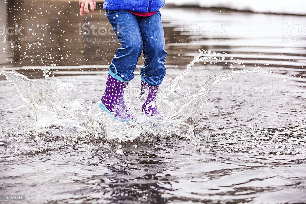 Young Girl Jumping in Puddle stock photo