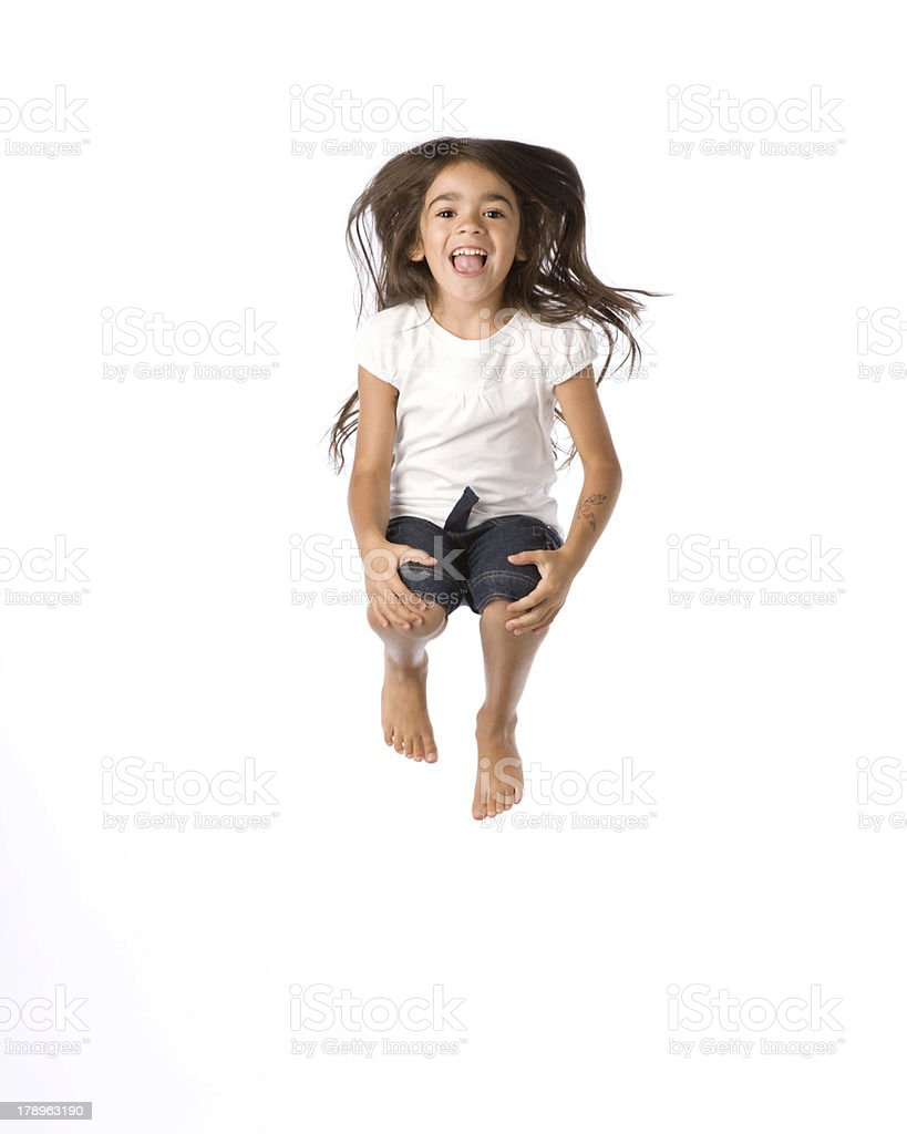 Young girl jumping in the air and holding knees stock photo