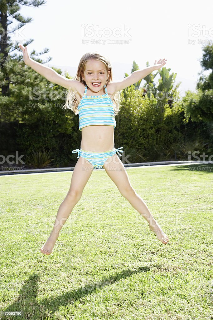 A young girl jumping in the air outdoors royalty-free stock photo