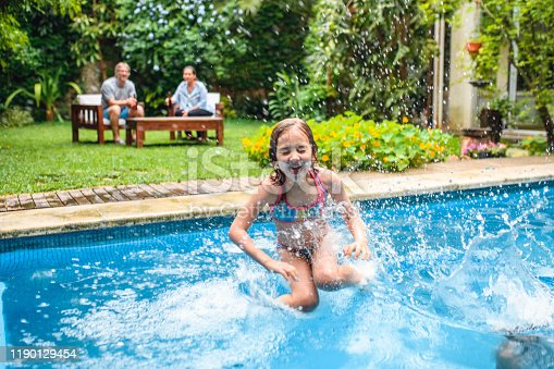 Close-up of laughing young girl with eyes shut jumping into backyard swimming pool and making big splash.