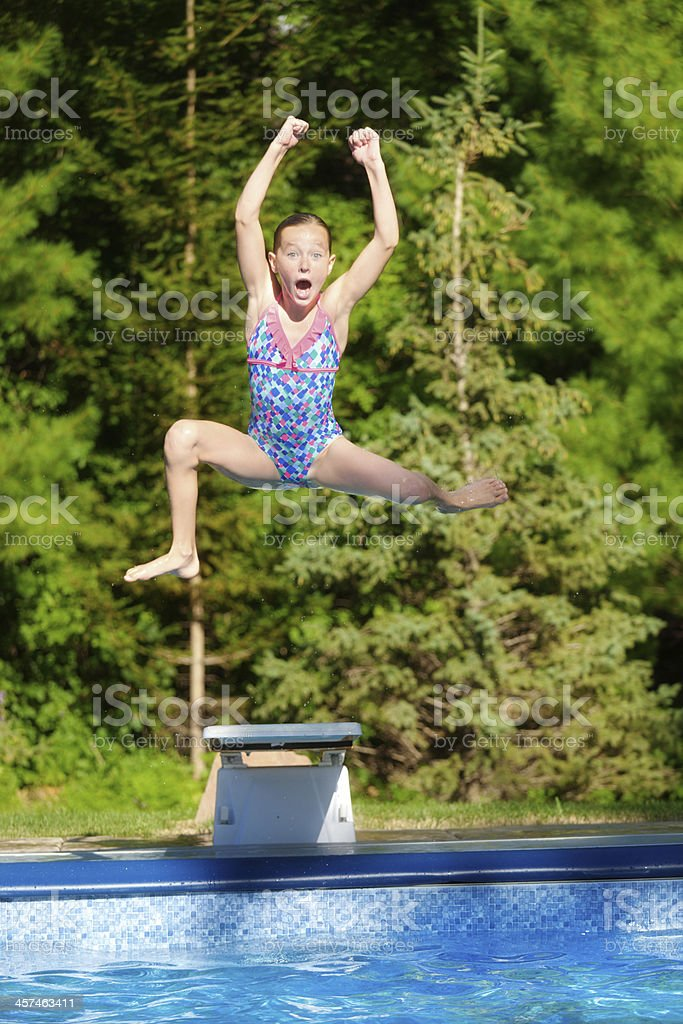 Young Girl Jumping Off Diving Board Into Summer Swimming Pool Stock Photo More Pictures Of 10