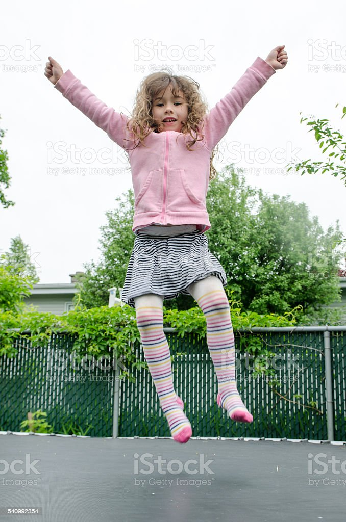 Young girl jumping on trampoline in backyard stock photo