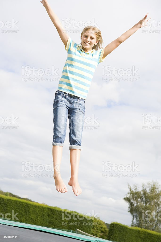 Young girl jumping on trampoline smiling royalty-free stock photo