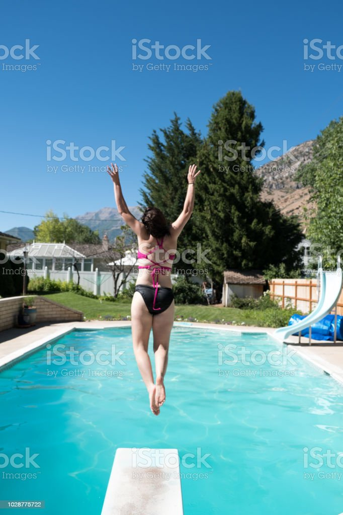 Young Girl Jumps Off Diving Board Into A Backyard Swimming ...