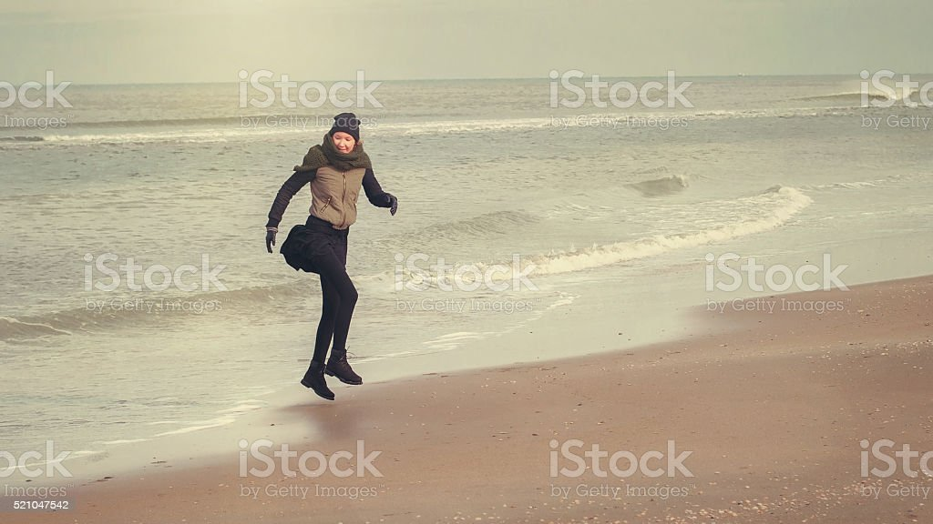 Young girl jumps on the seashore stock photo