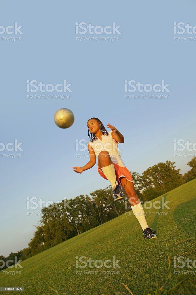 Young Girl Kicking Soccer Ball/Football royalty-free stock photo