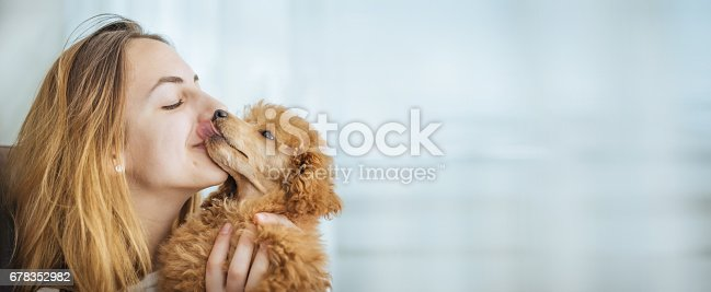 istock Young girl kissing her good friend dog . 678352982