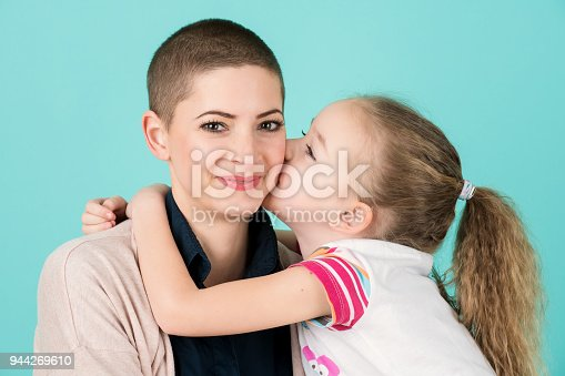469949126 istock photo Young girl kissing mother, young cancer patient, on the cheek. Cancer and family support concept. 944269610