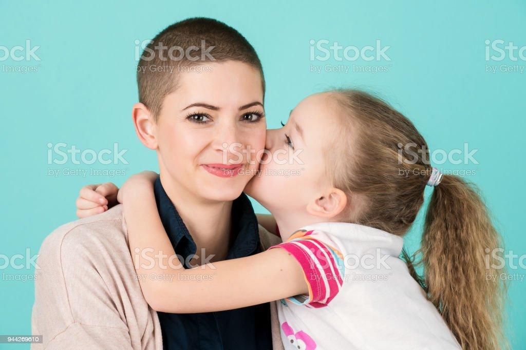 Junges Mädchen, Mutter, junge Krebspatienten auf die Wange küssen. Krebs und Unterstützung durch die Familie Konzept. – Foto