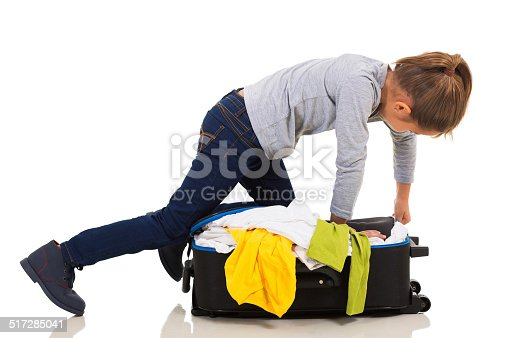 926982852 istock photo young girl kneeing on suitcase trying to zip it up 517285041