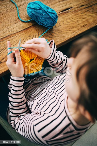 Young girl knitting a circle scarf with yellow and blue coloured yarn sitting at the wooden table. View from above over the shoulder.