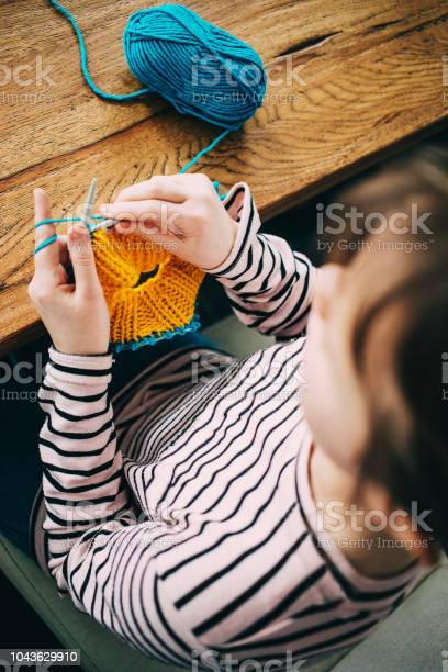 Young girl knitting a circle scarf with yellow and blue coloured yarn picture id1043629910?b=1&k=6&m=1043629910&s=612x612&h=mmgwope8hbcuhja80jgwxgmfee273evokwlj6quovuw=
