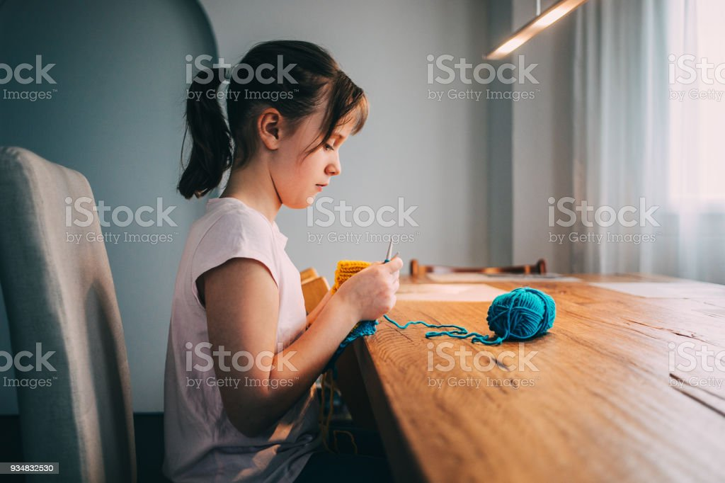 Young girl knitting a circle scarf with yellow and blue coloured yarn. Sitting at the wooden table, side view. stock photo