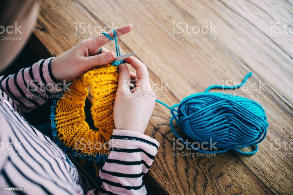 노랑, 파랑 색의 원사 원 스카프를 뜨개질 하는 어린 소녀. 나무 테이블에 앉아 뜨개질 바늘 닫습니다. - 로열티 프리 가을 스톡 사진