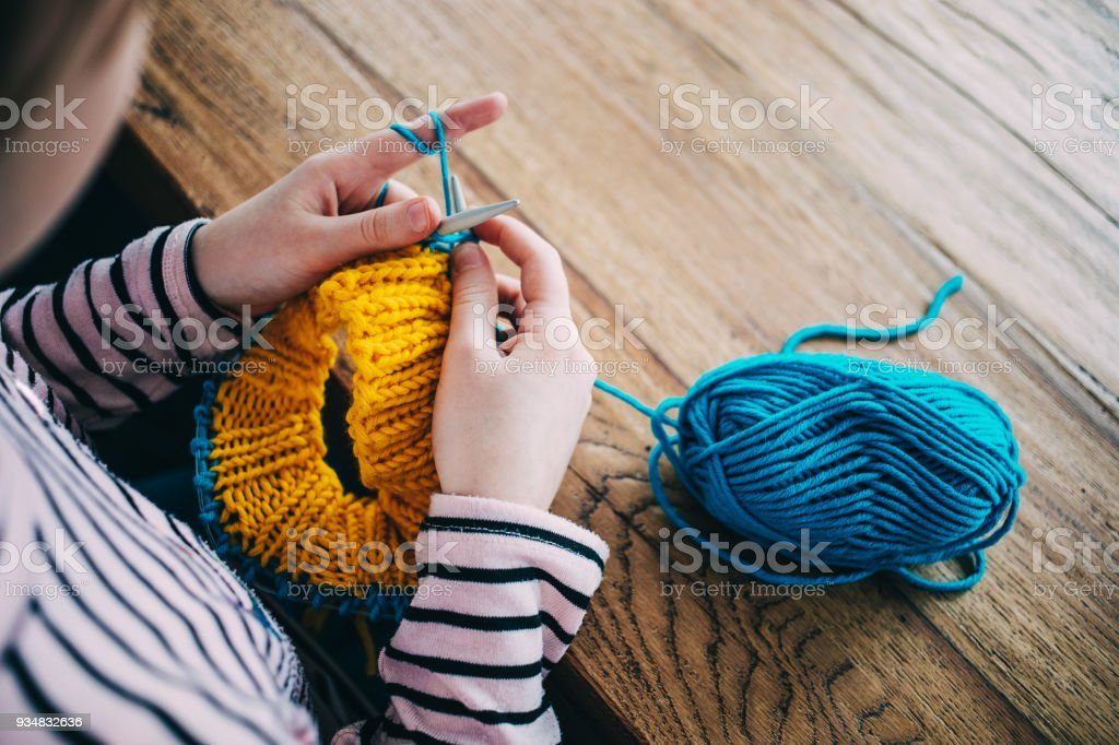 Young girl knitting a circle scarf with yellow and blue coloured yarn. Sitting at the wooden table, close up of the knitting needles. stock photo