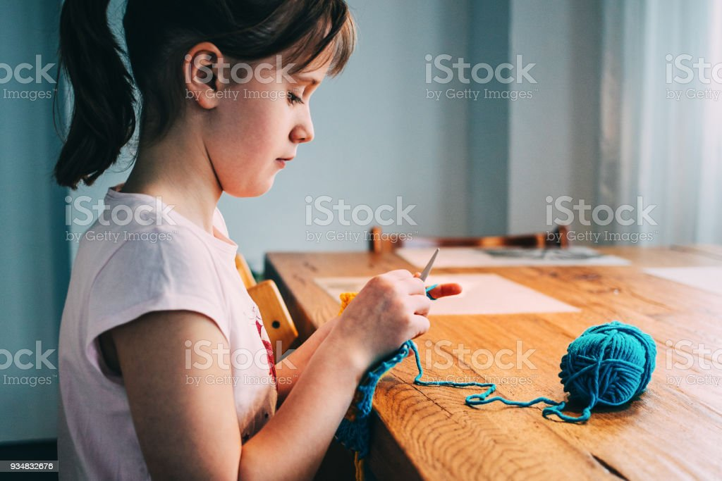 Young girl knitting a circle scarf with yellow and blue coloured yarn. Sitting at the wooden table, side view, close up. stock photo