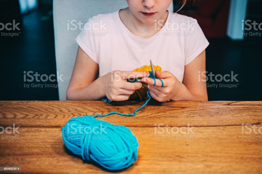 Young girl knitting a circle scarf with yellow and blue coloured yarn. Sitting at the wooden table, front view, close up. stock photo