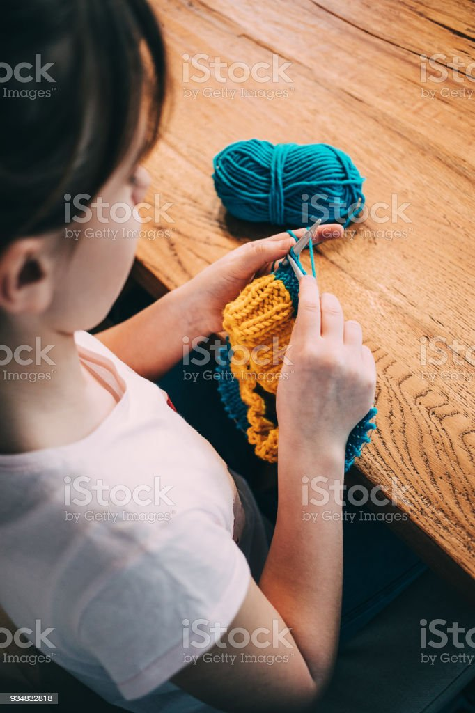 Young girl knitting a circle scarf with yellow and blue coloured yarn. Sitting at the wooden table, close up over the shoulder. stock photo