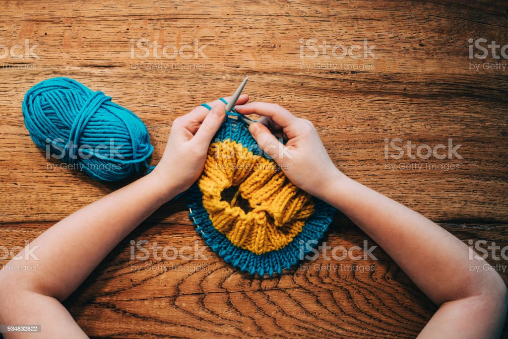 Young girl knitting a circle scarf with yellow and blue coloured yarn. Sitting at the wooden table, view from above, close up. stock photo