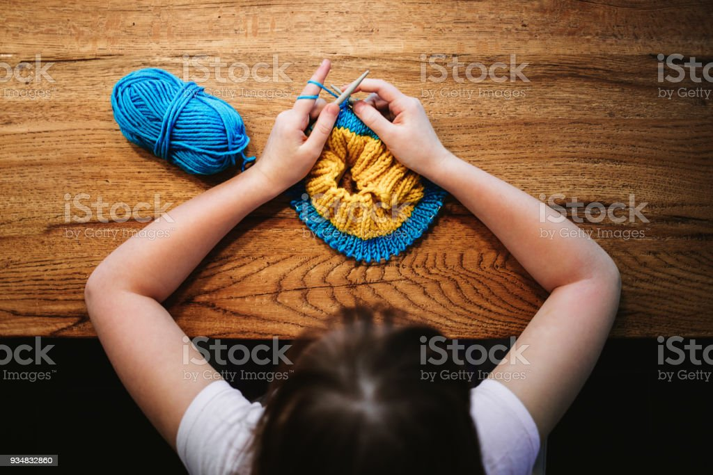 Young girl knitting a circle scarf with yellow and blue coloured yarn. Sitting at the wooden table, view from above. stock photo