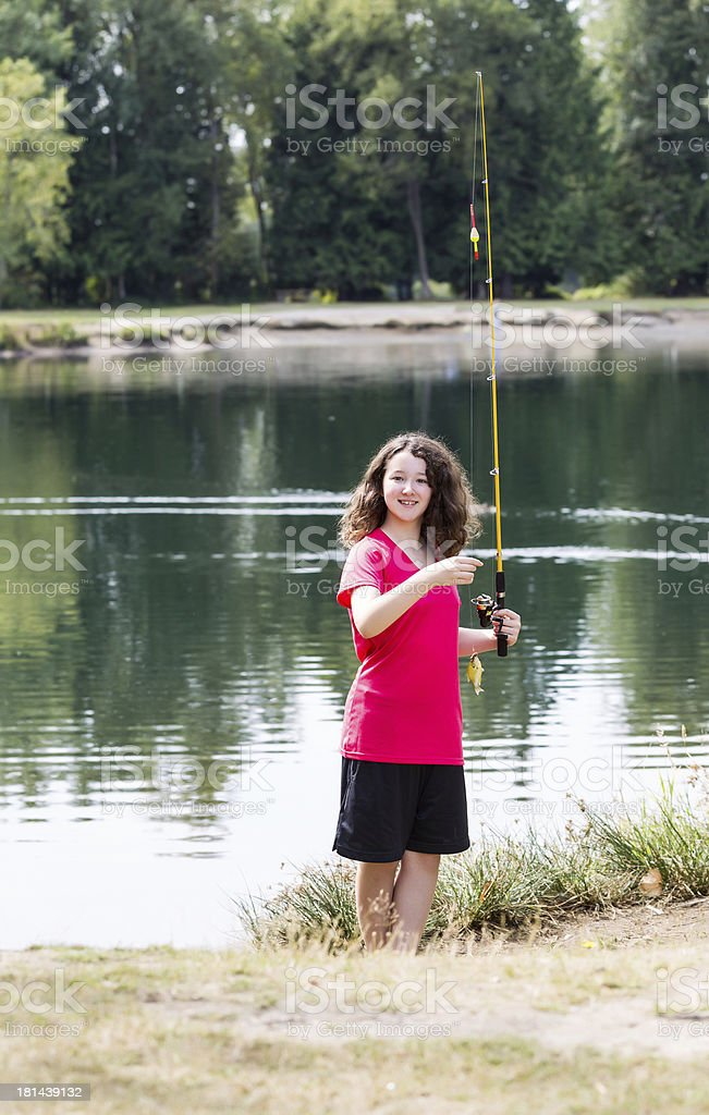 Young Girl lands little fish royalty-free stock photo