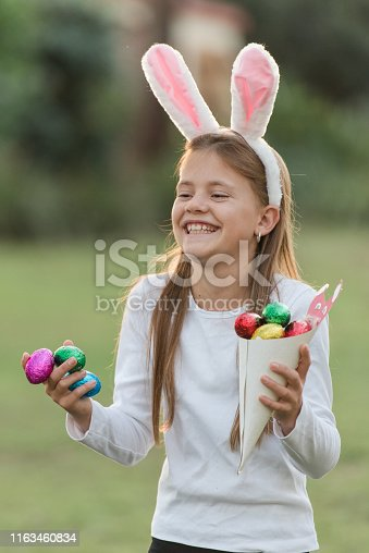 istock Young girl laughing looking for Easter eggs at Easter egg hunt 1163460834