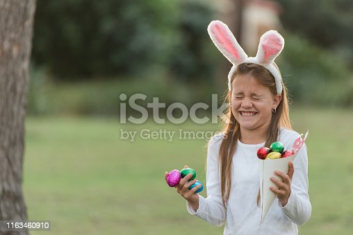 istock Young girl laughing looking for Easter eggs at Easter egg hunt 1163460910