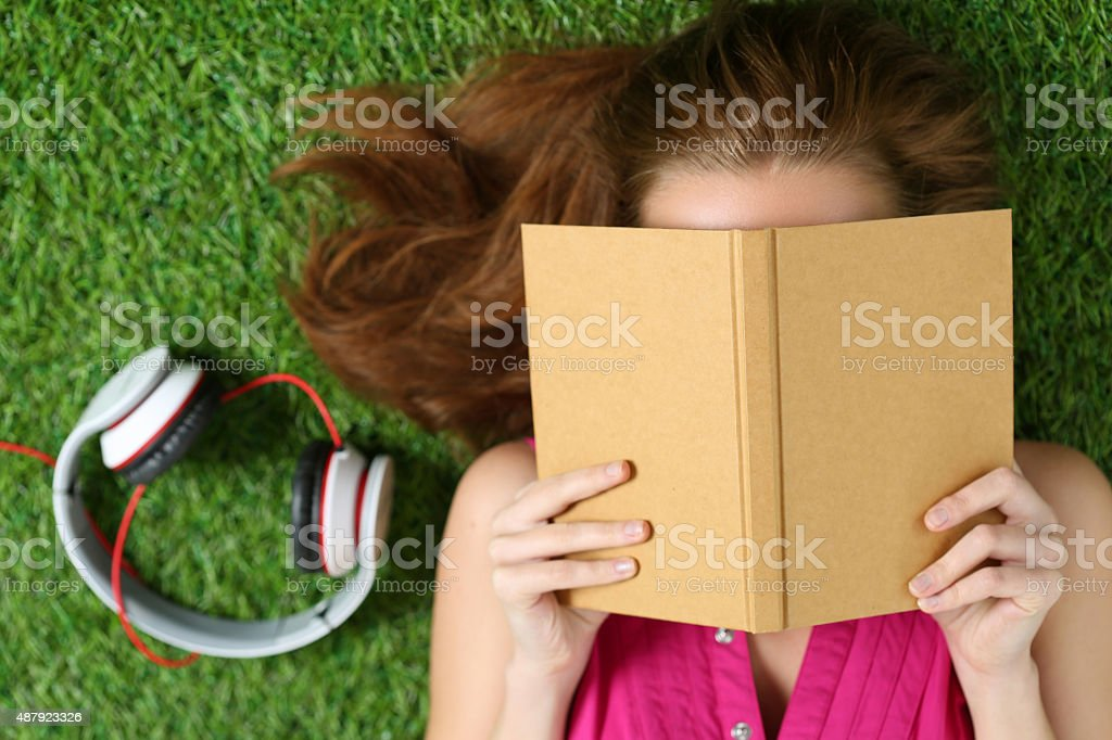 Young girl laying on grass in park holding a book stock photo