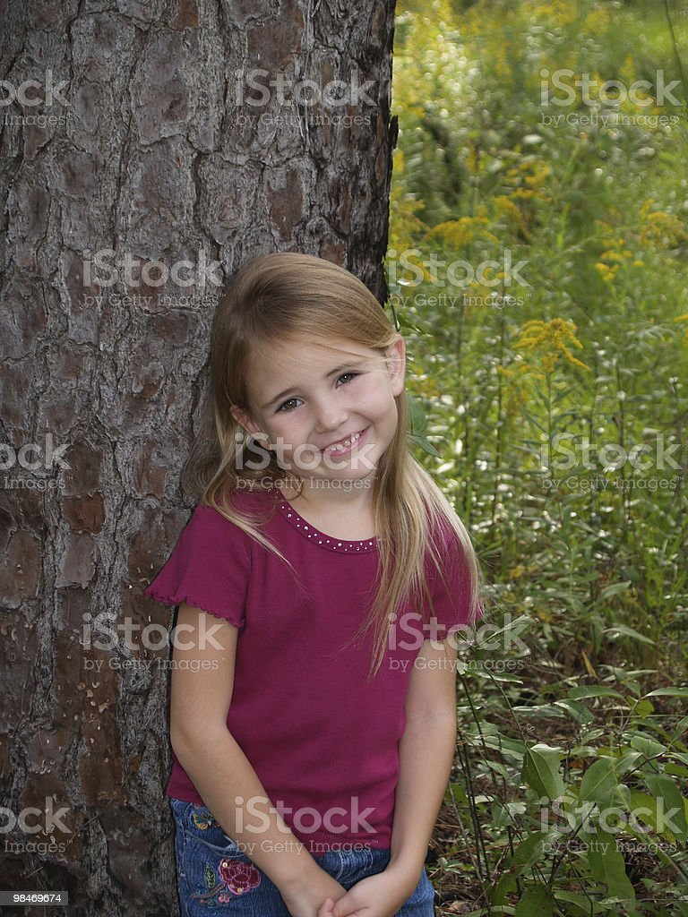 Young girl Leaning Against Tree royalty-free stock photo