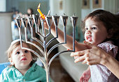 Young girl lights the Hanukkah menorah with help from adult